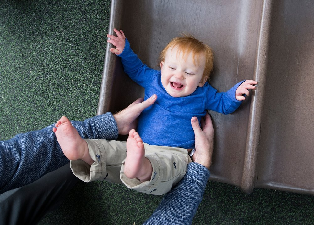 A toddler laughs while going down a slide at a park in Denver, Colorado.