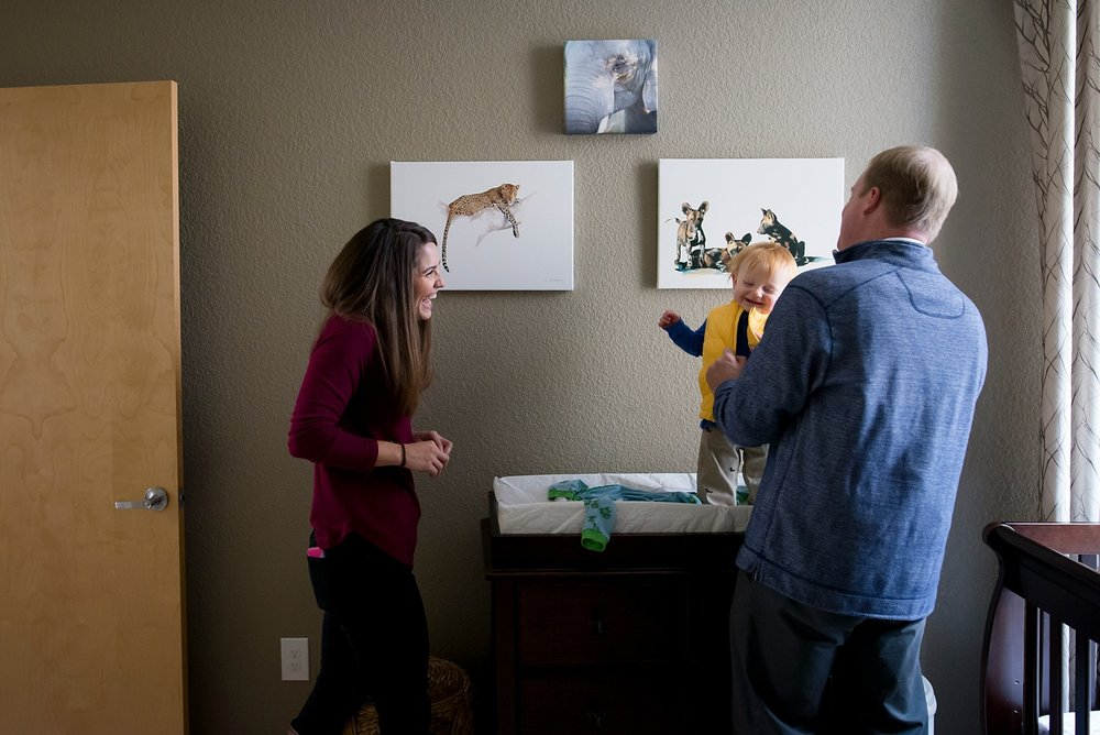 A family laughs while they get their baby ready to go to the park in Denver, Colorado.