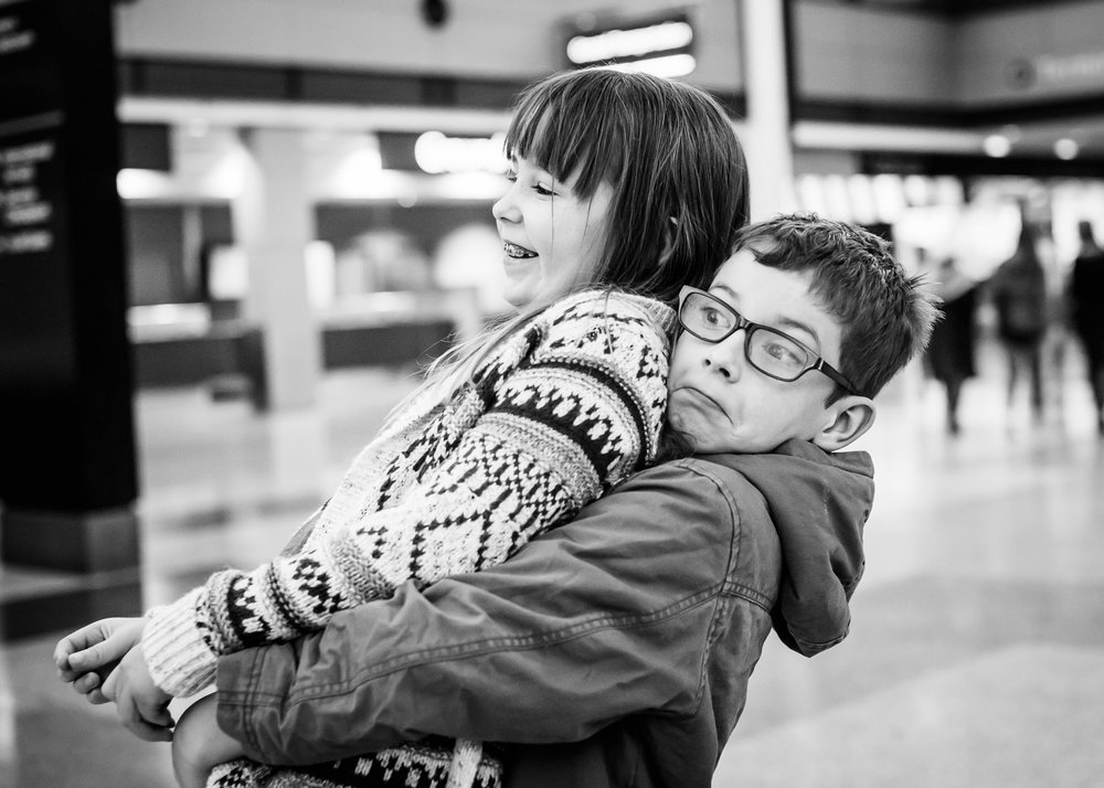 A brother and sister horse around at Denver International Airport.  The photographer, Kristiina Craven, reviews Bella Baby Photography.