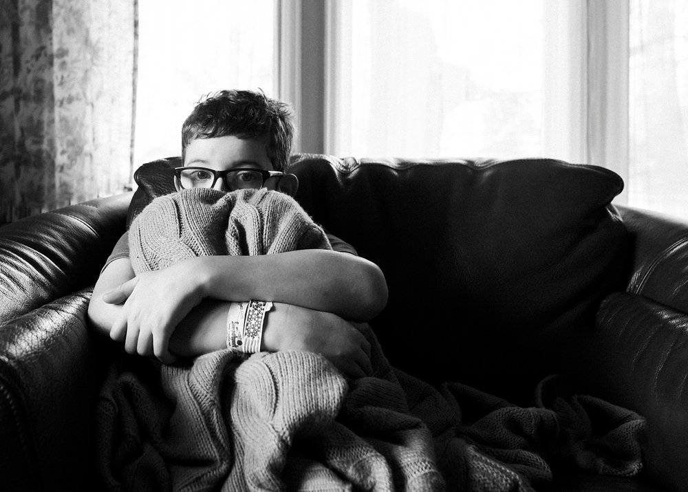 A black and white photo of a boy snuggled in a blanket peering at his mom, photographer, Kristiina Craven in Denver, Colorado.  This photo appeared in a post on unschooling on her blog.