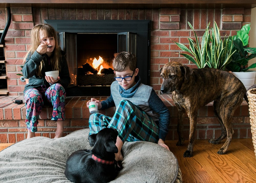 "A boy and a girl eat treats by the fire with their dogs during their ""deschooling"" phase of unschooling in Colorado."