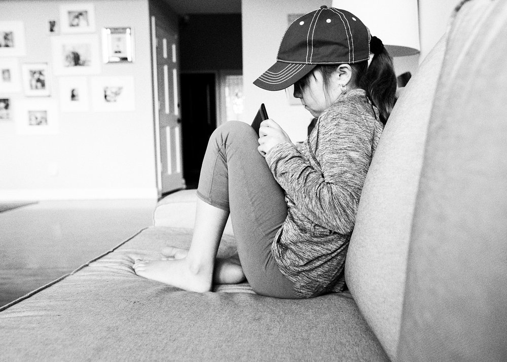 A young girl plays games on an ipad on a couch.  She is deschooling before she transitions into unschooling with her family in Denver, Colorado.