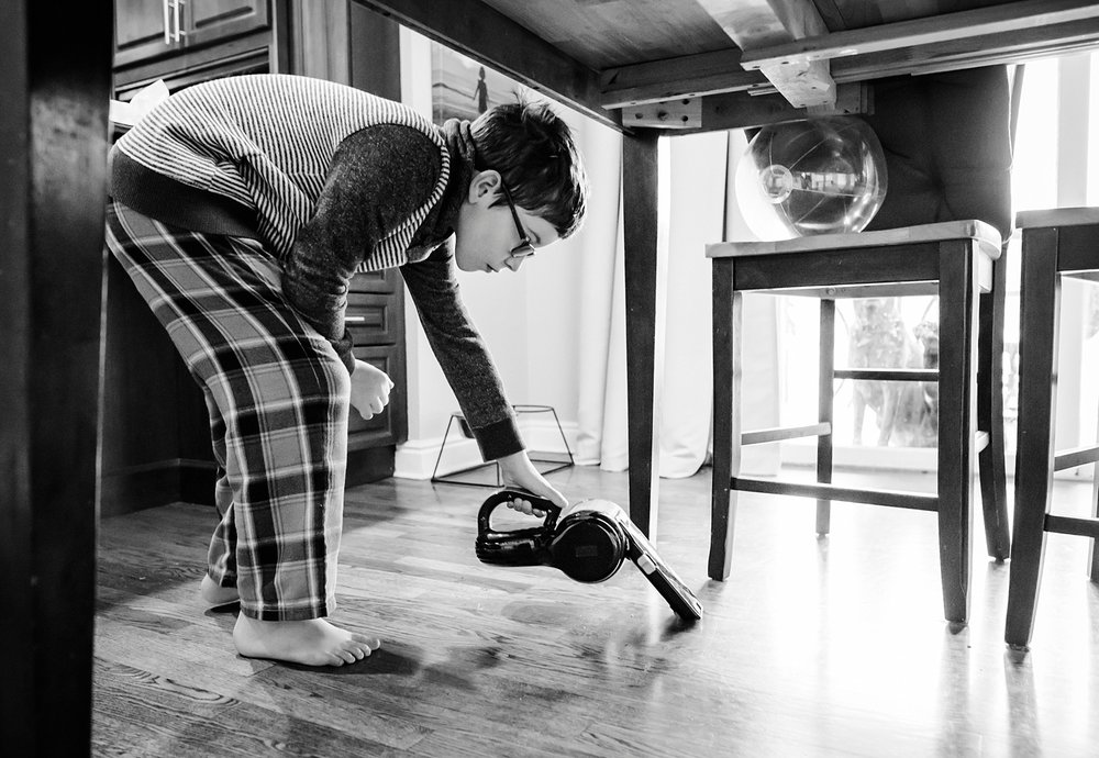 A boy vacuums under the table in his pajamas--a perk of unschooling! | GettingUnschooled.com