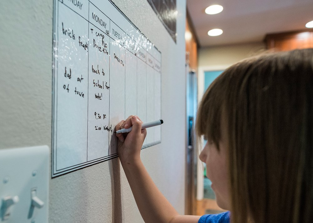 A girl fills in the weekly schedule during a family meeting.  Incorporating family meetings intou our regular routine is part of our unschooling plan for this year. | GettingUnschooled.com
