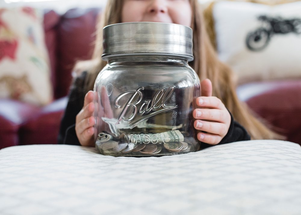 A girl hold's the family piggy bank used for spare change and dollars found in pockets and around the house. This post about planning for the unschooled year are on the blog: GettingUnschooled.com.
