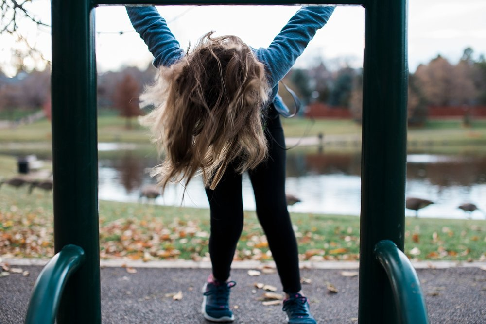 Our daughter flips on a bar at a local park during homeschooling recess.  | GettingUnschooled.com
