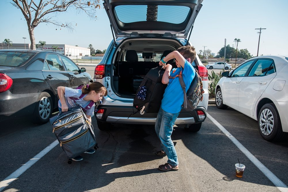 Townes and Kate load up the suitcases to the rental car before heading home after a roadschooling adventure to LA. I used to think I could never homeschool, but now we are all reaping the benefits of unschooling and we are so happy! More mindshifts I made once we started to homeschool. | Getting Unschooled is a blog about homeschool, roadschool and unschool adventures of a family of four in Denver, Colorado.