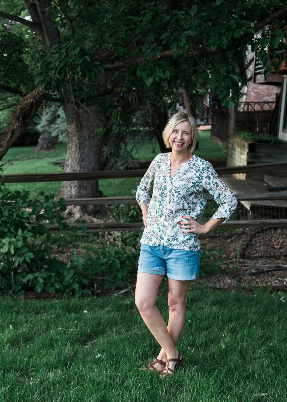 Baggy denim shorts, a feminine top, and comfy sandals is an easy summer outfit for women over 40.