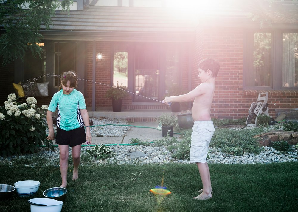 Siblings have a water balloon fight in the yard to stay cool.
