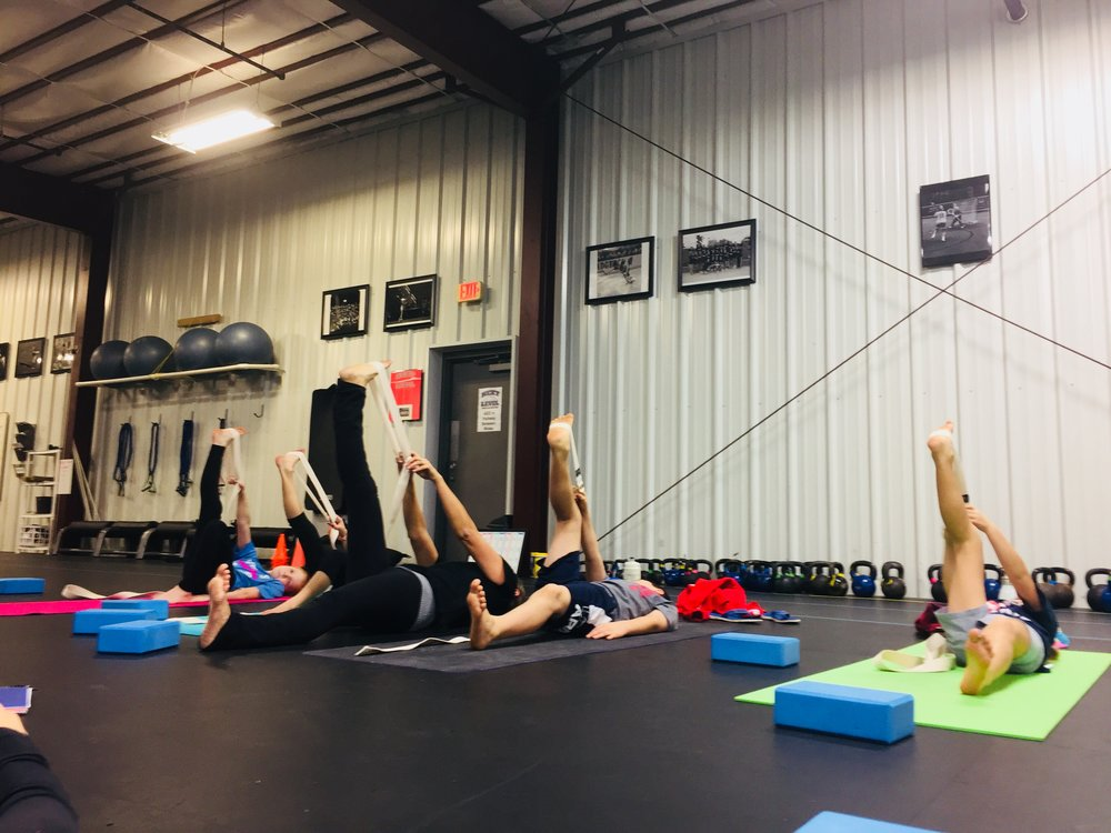 Working with yoga straps in our Yoga for Athletes class.