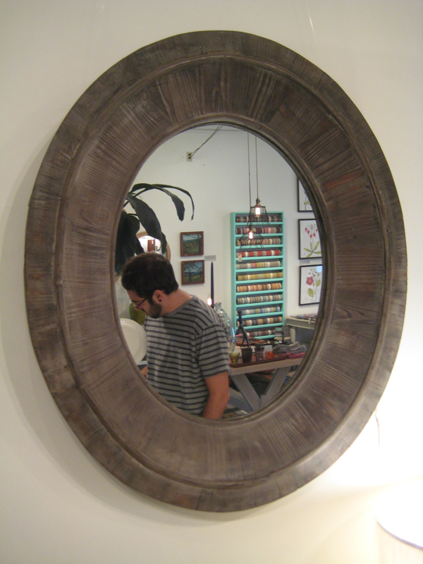 Logan reflected in wood mirror.