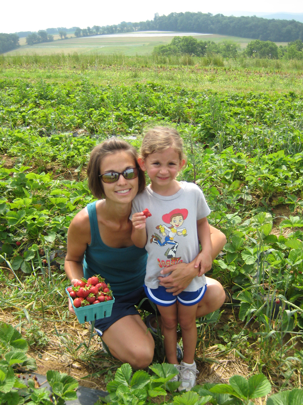 Ann Marie and Isabella with a full basket of strawberries!