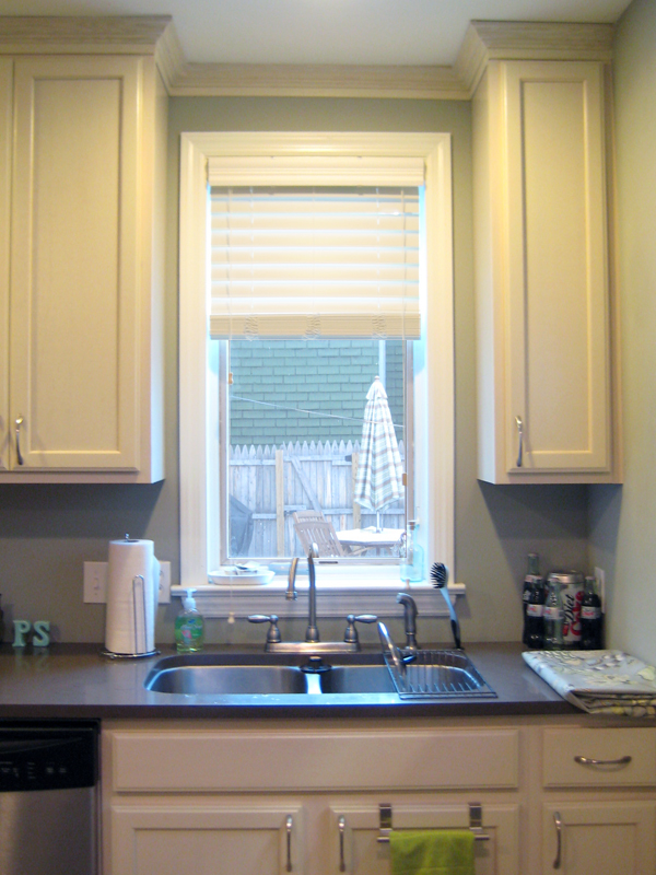 Window over the sink with white wooden blinds.