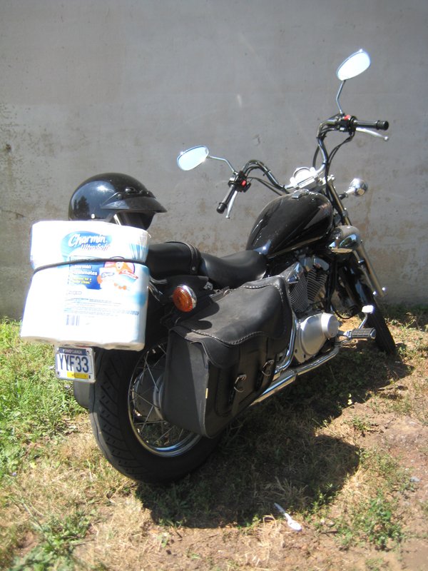 A photo of a motorcycle with toliet paper bungeed onto it.