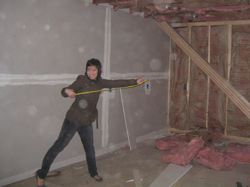 View of Valerie in kitchen with tape measure during renovation