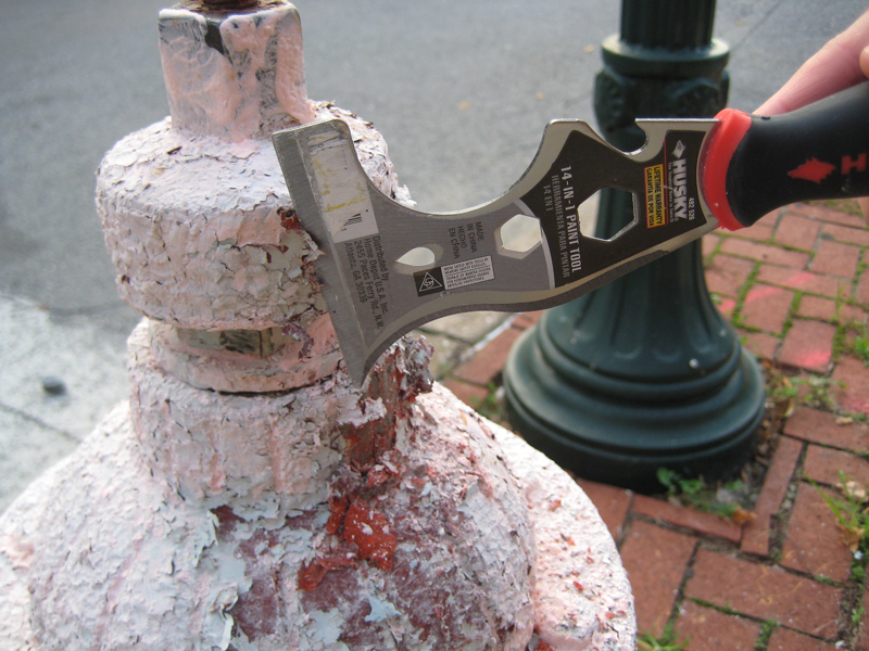 Scraping the paint off of hydrant.