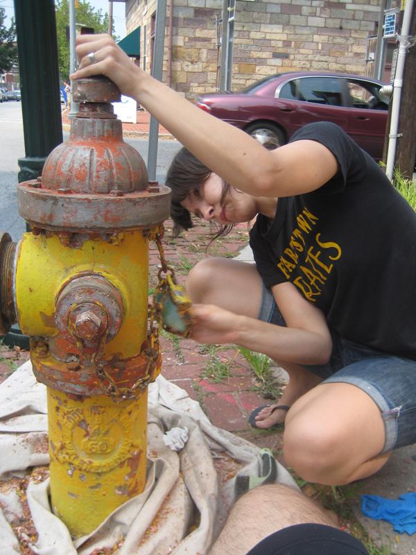 Valerie sanding the hydrant.
