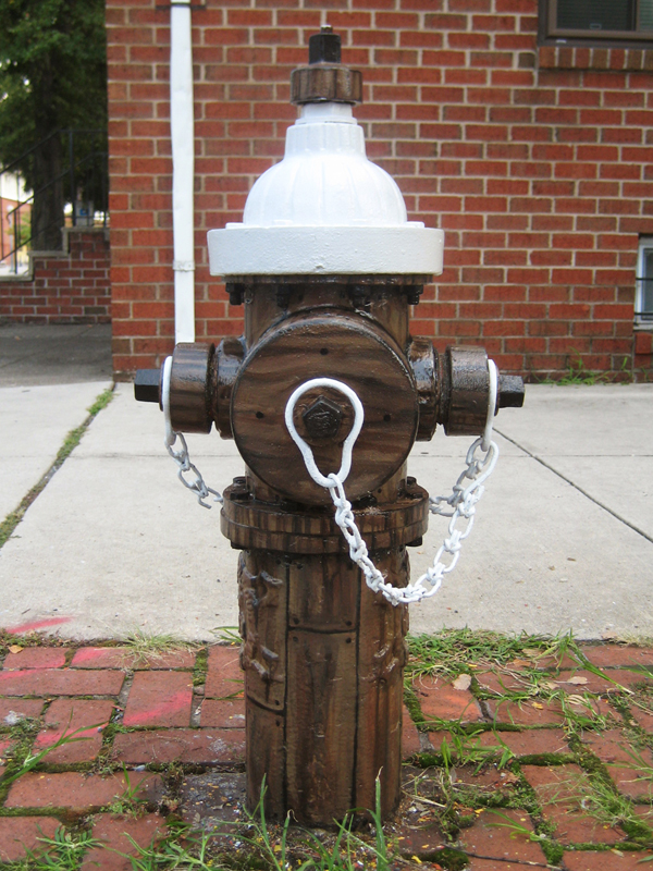 Fire hydrant painted to look like wood.
