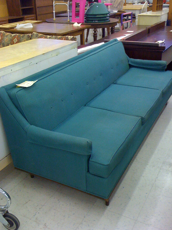 Blue-green mid-century modern sofa in thrift store.