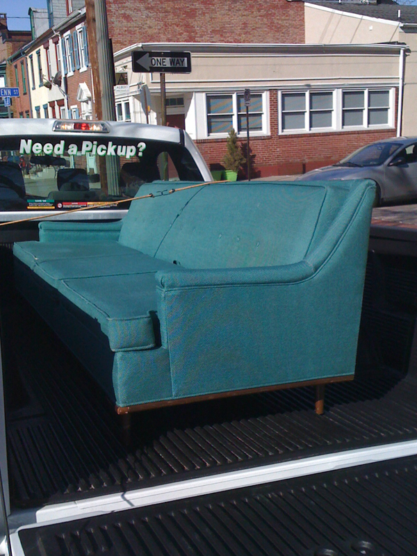 Blue-green mid-century modern sofa in pick-up truck.