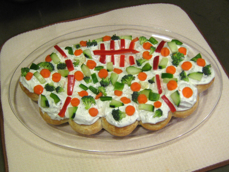 Football shaped dinner rolls with dip and vegetables on top.