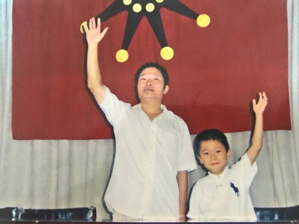 Zhu (right) waves to the camera with his father (left).