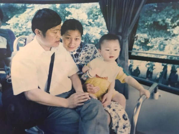 Keith Zhu (right) sits with his parents when he was a child.