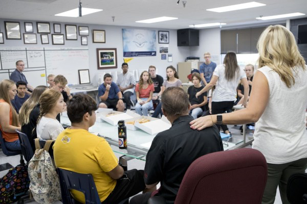 The Feather staff meets once a month in the publications lab to train, plan, review and organize the newspaper expectations. Advisers Greg Stobbe, seated left, and Kori Friesen, right, help lead but rely on the editors to run the meetings.
