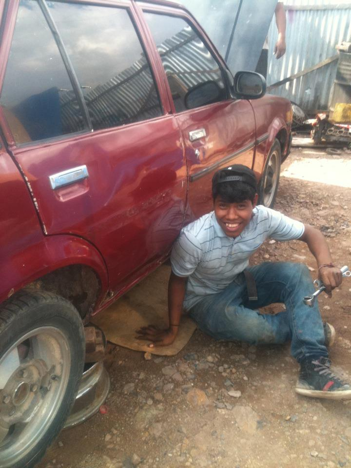 Geovanny working at a mechanic's shop for his vocational training.