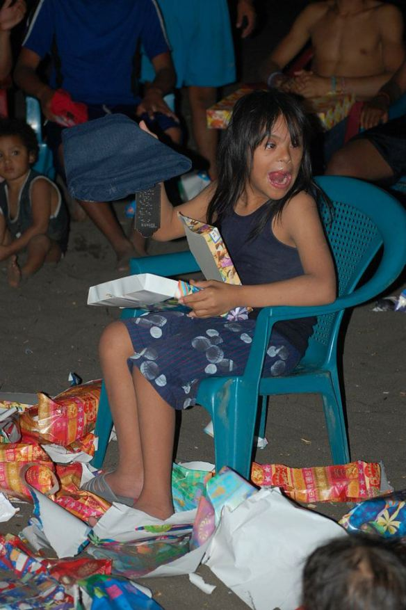 Brayan opens his presents during last year's beach Christmas