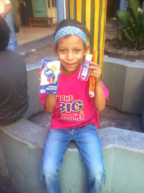 Leticia and her mother worship with Breaking Chains on Sundays. Here she poses with a few school supplies that were provided to her through a donation.
