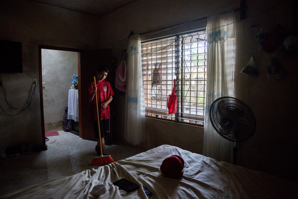 Luis Lara, 12, sweeps up after being told to get off of his phone and help around his aunt and uncle's house in Hoctún, Yucatán. Luis came from Dallas to live with his family and learn Spanish for the summer.