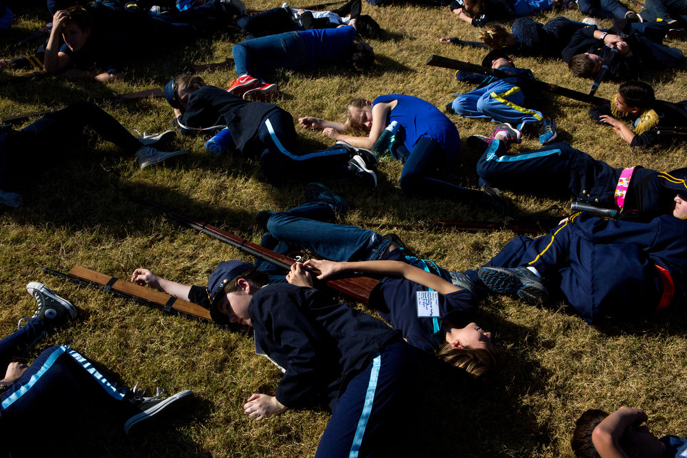 Students at Desert Shadows Middle School pretend to be dead in the grass at Sereno Park during the annual 7th-grade reenactment of the Battle of Gettysburg on Nov. 17, 2016. Lying next to them are the homemade wooden guns required for their class grade.