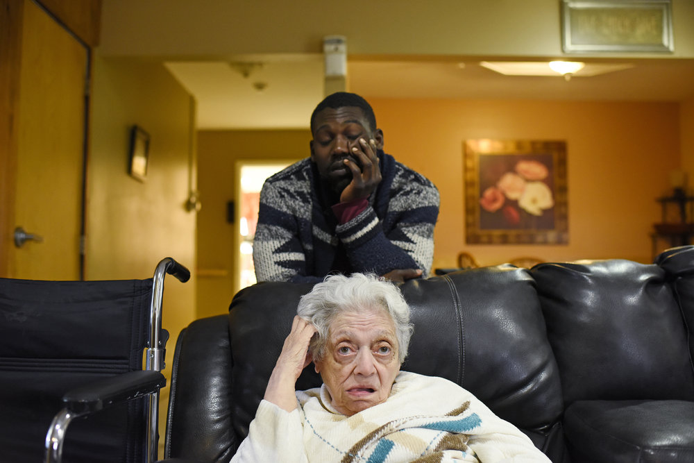 Relief day service provider, Maurice Thomson (29), sits behind Evelyn Vius (83) at a Sullivan Arc residential house in Woodridge, New York on Oct. 9, 2016.