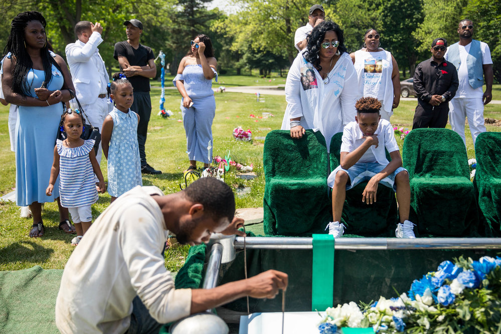 "Family members watch as Jechon Anderson's casket is lowered, during the funeral for the 11-year-old, at Mount Hope Cemetery, on Saturday, June 16, 2018, in the South Side of Chicago. He would rap about ""putting guns down"" with his stepfather before he was ultimately shot in the head. Anderson was the youngest person killed by gun violence in Chicago this year and police are still investigating his homicide. Anderson is to be buried next to his grandmother who he lived with as a baby, until 2009 when she died of cancer."