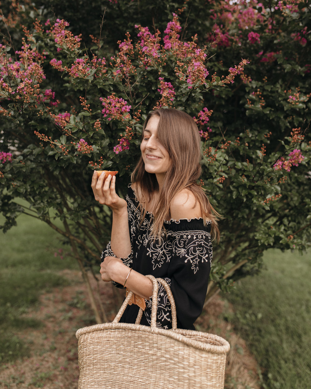 Eating a peach with a big woven handbag, Emily smiles as she incorporates habits that brighten her days