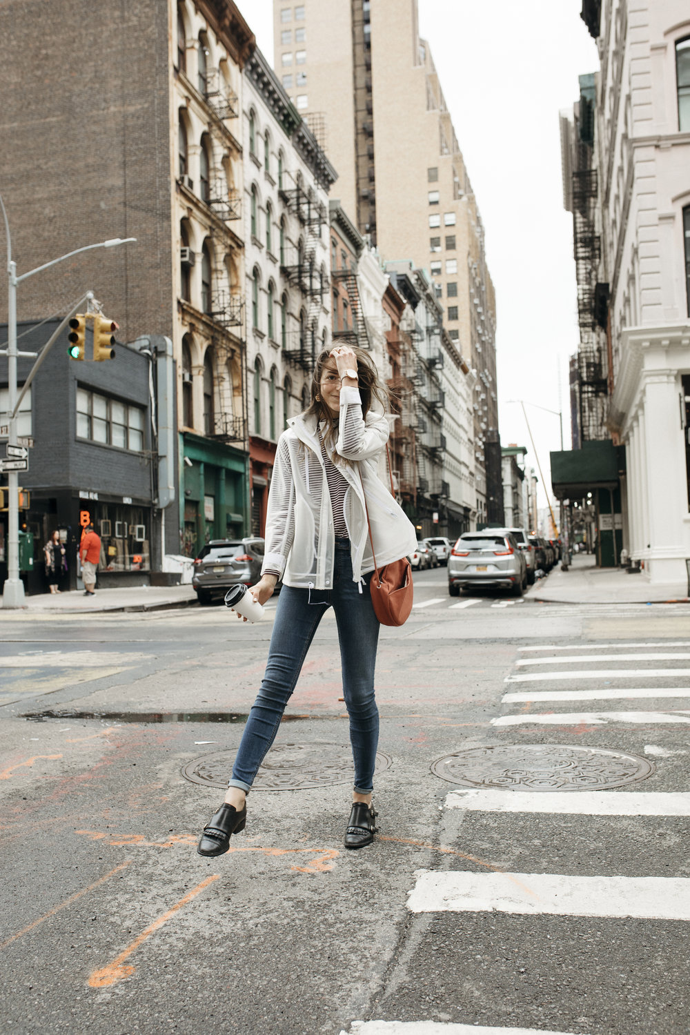 In a white jacket, coffee cup in hand, the blogger steps out onto the streets of NYC and crosses a sidewalk in a quiet area