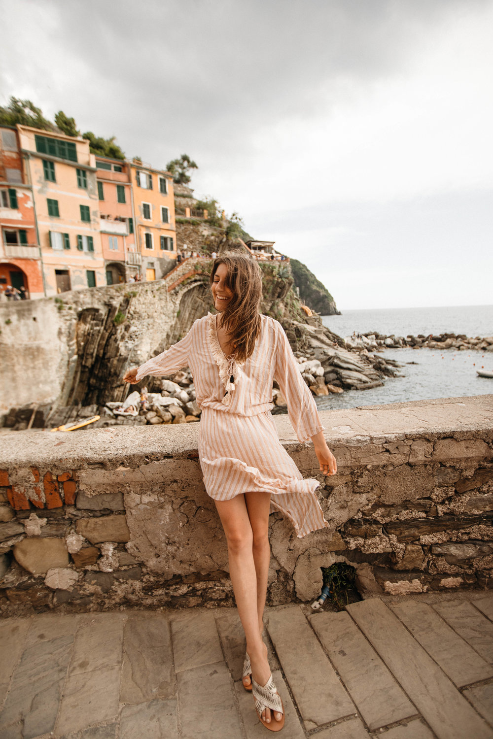 Gazing out over the brilliant open ocean in a bright sundress during a trip to Europe