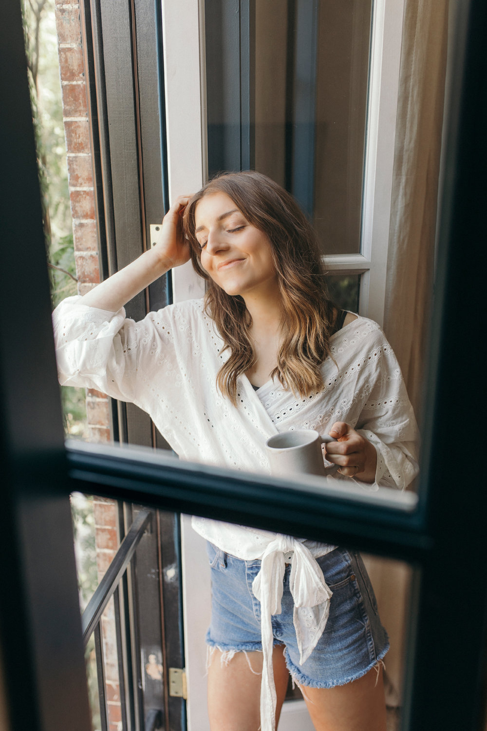 Relaxing next to a large window taking in the glow of the sun, beautiful nature, and fresh air, coffee cup in hand of course!