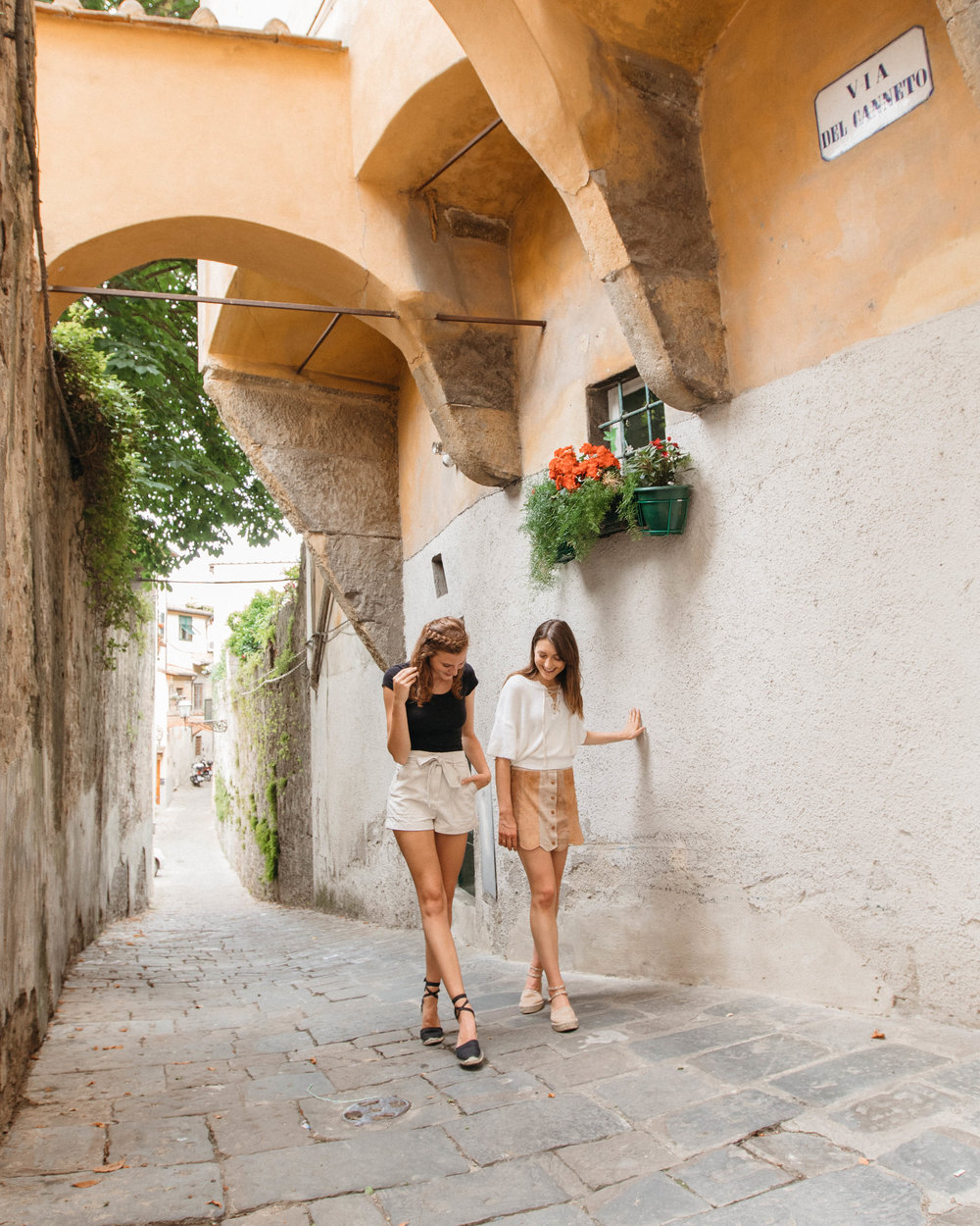 Travel blogger friends in little streets of Italy.