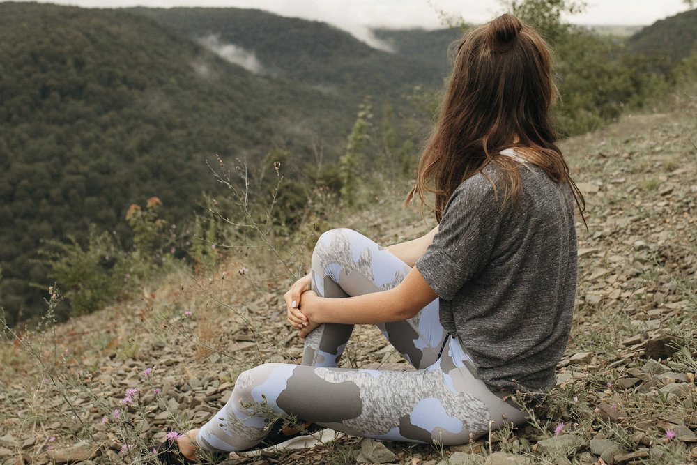 Emily looks out over beautiful mountains in fashionable arie leggings