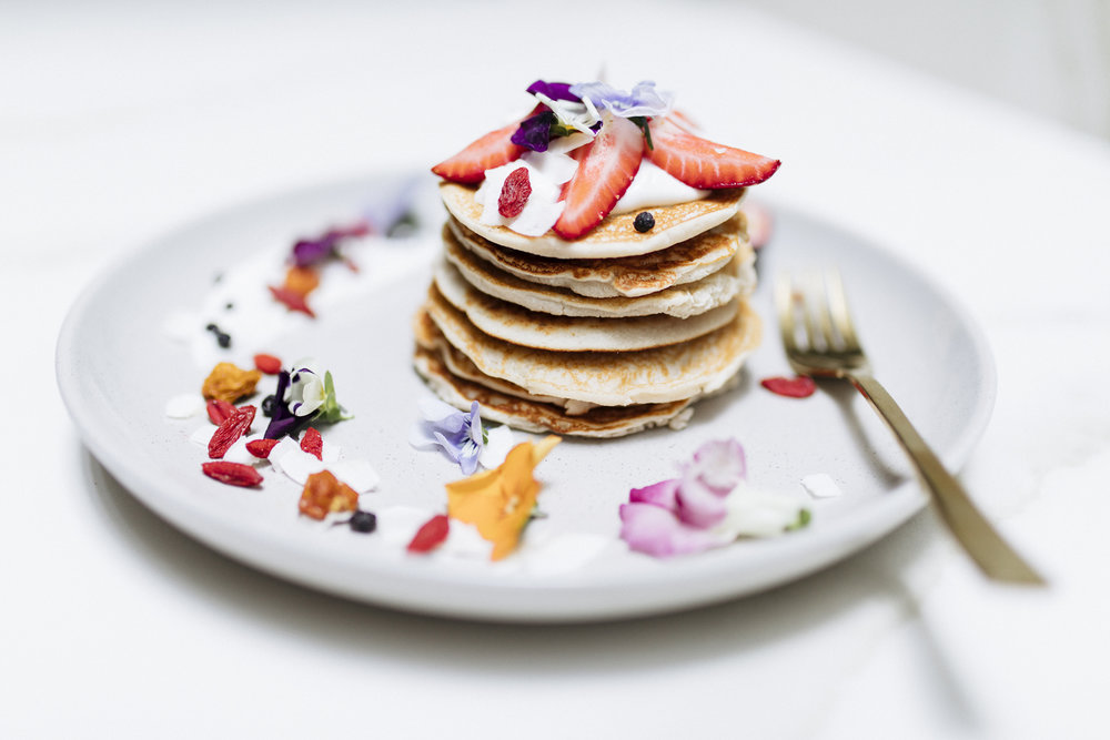 Vegan, dairy free, gluten free fluffy pancakes decorated with fruit and flowers to brighten up your morning!