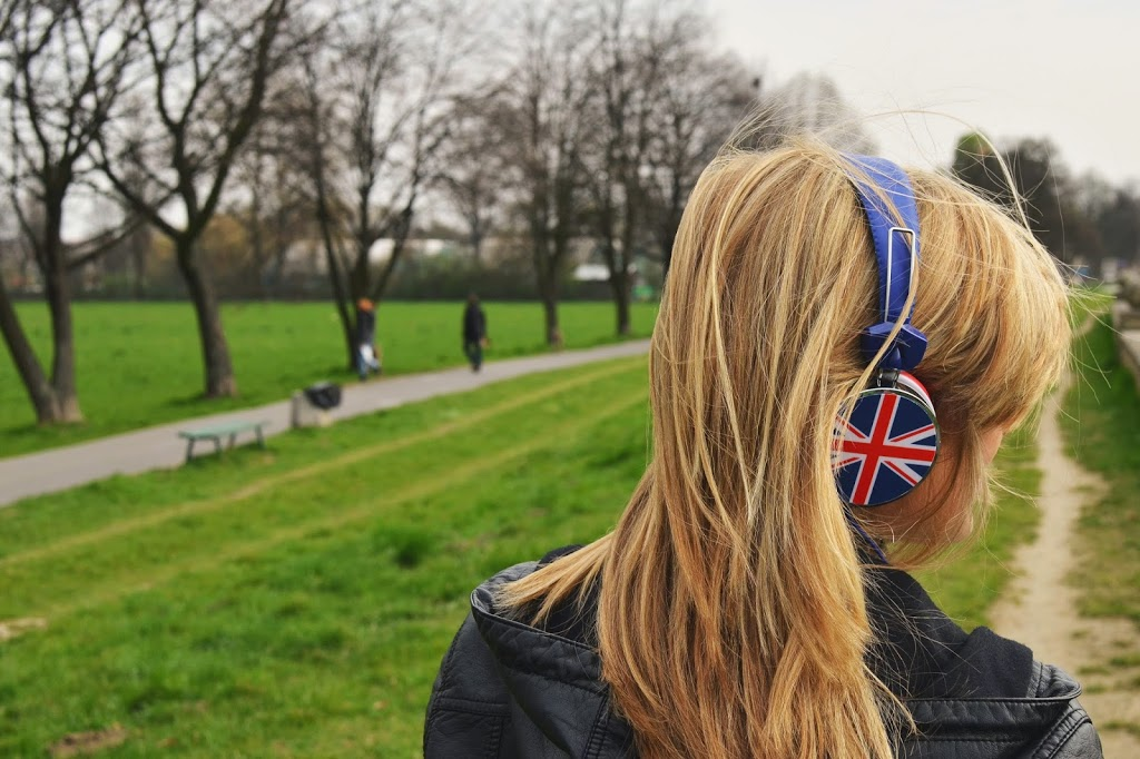 Woman in Park Listening to Music with Union Jack Headphones