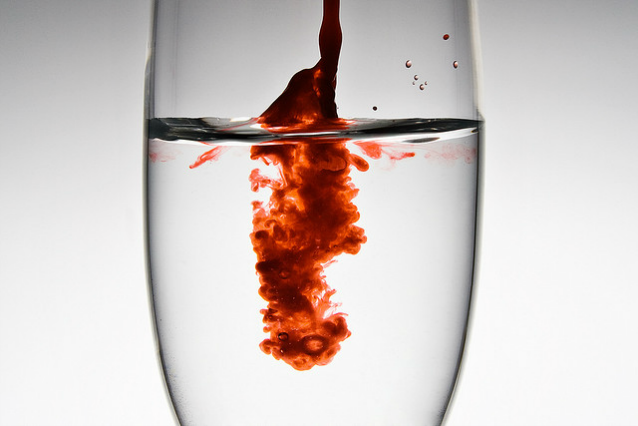 blood dripping into a glass of water