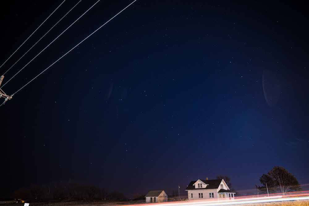 Night long exposure abandoned house and light trails from cars omaha nebraska