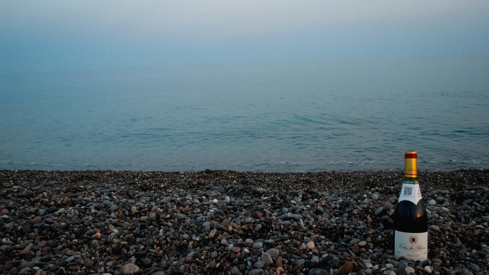 wine bottle in gravel beach nice france