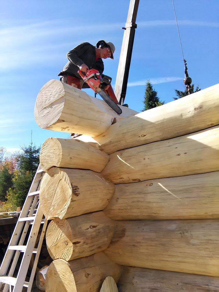 Brushing saddle notch with chainsaw on log cabin wall. - Near North Log Homes