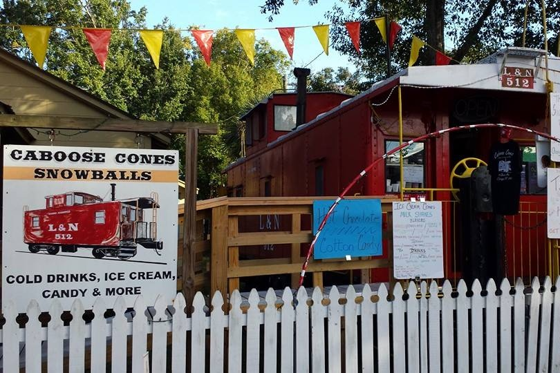Caboose Cones - 1009 Desoto St. Ocean Springs, MS 39564Caboose Cones is one of the most magical places in downtown Ocean Springs! Located in a red caboose in the owners' backyard, this snow cone stand boasts New Orleans-style snow cones, picnic seating area, and even a playscape for the kids! This is a classic, local spot to grab a cold, sweet treat during the summer after a bike ride or beach trip. Yum!