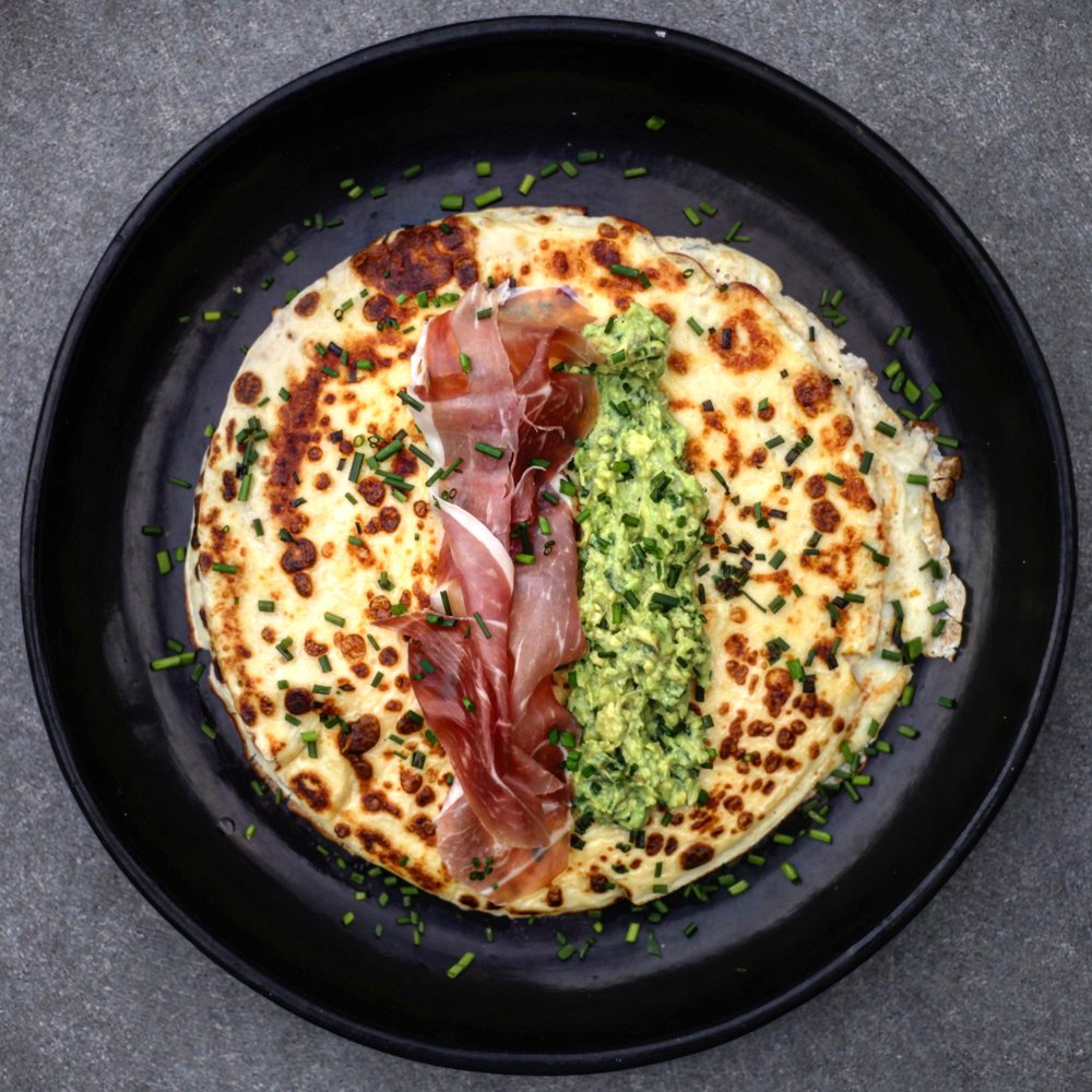 Cooking Time (includes preparation time): 30 Minutes Makes 8 Pancakes Ingredients: 1 Lemon - £0.30 Bunch of Chives - £0.70 3 Large Avocados - £3.00 1 Pack of Parma Ham - £2.65 500g Plain Flour - £0.40 1 Pint of Whole Milk - £0.45 6 Large Eggs - £1.25 Total Cost – £8.75 Method: 1.  Halve avocados and place flesh into a bowl. Add the juice of 1 lemon, some salt, pepper and olive oil. Finely chop a small handful of chives. Add them to the avocados. Mash. 2. NOW FOR THE PANCAKE BATTER. Place 100g of plain flour, 2 large eggs, 200ml of whole milk and 100ml of cold water into a bowl. Beat it all together until there are no lumps of flour. Add a small handful of chopped chives into the mix. 3. Place a frying pan on a medium to high heat. Then, pour in some olive oil, a couple of teaspoons. Ladle in the first helping of pancake mix. It should cover the base of pan but be quite thin. 4.  Give it 1-2 minutes on each side, but just check with a spatula to see when the underside is cooked. 5.  Once cooked, spoon on some of your guacamole and a slice of Parma ham. Squeeze over a little lemon juice and add some more chopped chives. Done.