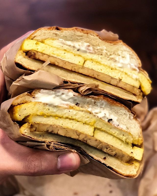 "It's been a while @orchardgrocer, but you taste exactly the same as we last met. 🤤😘💛 Pictured is their ""Bowery"" - their version of the breakfast sandwich with turmeric tofu egg 🍳, tempeh bacon 🥓 , and @violifeamerica provolone slice 🧀 on a fresh roll 🥖 , served with a choice of spicy or regular mayo 👌🏽👌🏽👌🏽 #vegan #breakfast #veganfoodshare #whatveganseat"